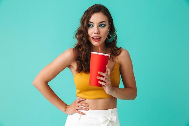 Mulher morena glamourosa usando brincos de moda, beber bebida ou refrigerante de palha e copo de papel vermelho grande Foto Premium