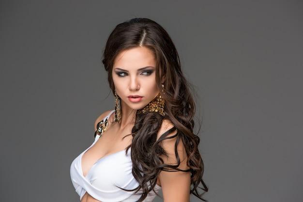 Mulher morena jovem sexy com o cabelo dela posando em um biquíni branco. estúdio Foto gratuita