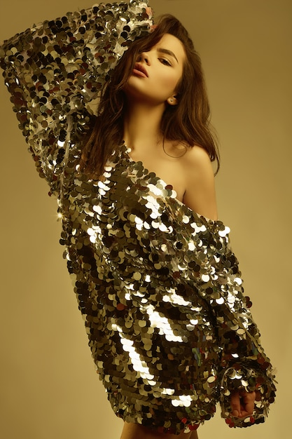 Mulher morena linda sensual em um vestido brilhante de moda de lantejoulas Foto Premium
