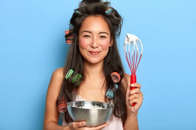 Mulher morena satisfeita com creme de leite azedo em uma tigela e usando rolos de cabelo Foto gratuita