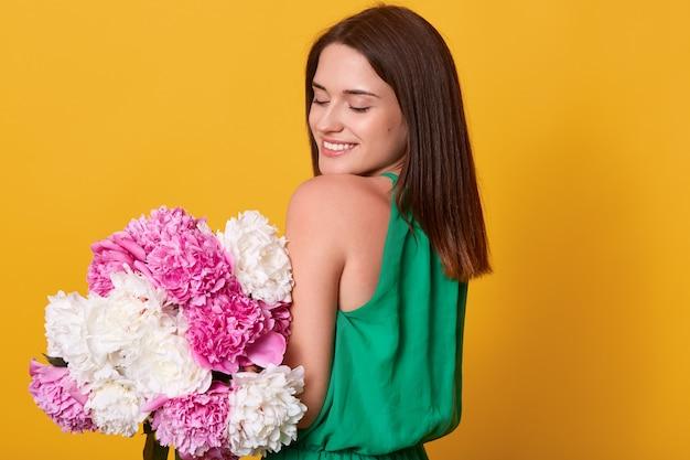 Mulher morena suave com vestido verde, segurando flores de peônia nas mãos Foto gratuita