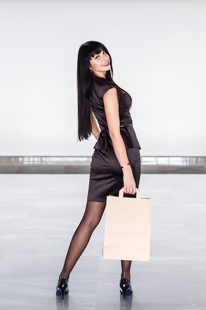 Mulher moreno de sorriso atrativa nova que guarda o saco de compras de papel, andando em uma alameda. Foto Premium