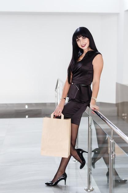 Mulher moreno de sorriso bonita nova que guarda o saco de compras de papel, andando em uma alameda. Foto Premium