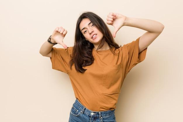 Mulher moreno nova que mostra o polegar para baixo e que expressa o desagrado. Foto Premium