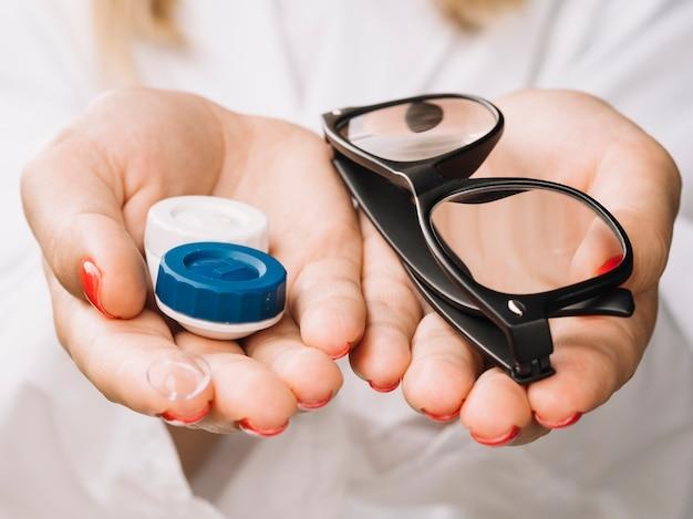 Mulher mostrando as lentes de contato da câmera e óculos Foto gratuita