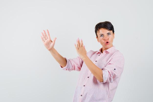 Mulher mostrando gesto de golpe de caratê em camisa rosa e parecendo poderosa. vista frontal. Foto gratuita