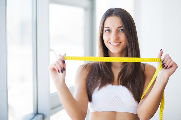Mulher mostrando na fita quanto peso ela perdeu Foto Premium