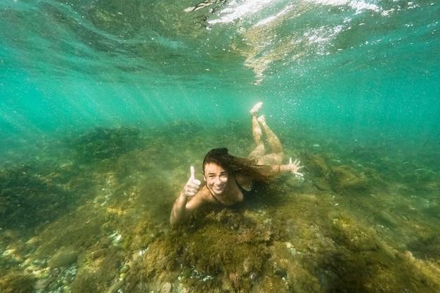 Mulher, mostrando, polegar cima, gesto, submarinas Foto gratuita