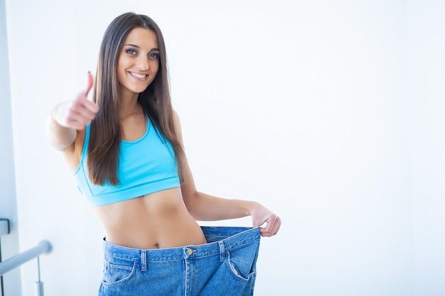 Mulher mostrando quanto peso perdeu Foto Premium