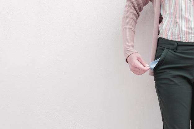 Mulher mostrando seu bolso vazio no fundo da parede. Foto Premium