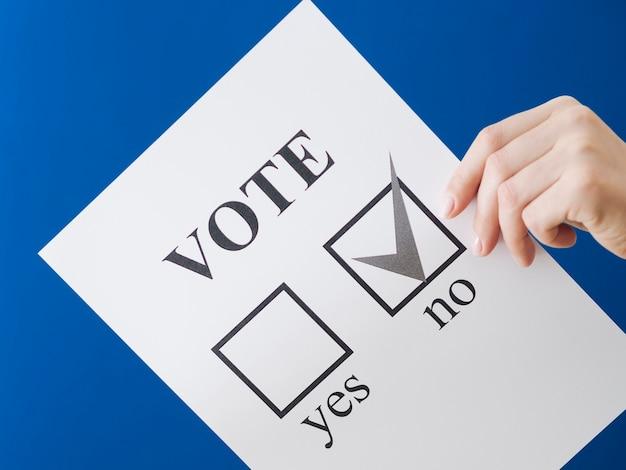 Mulher mostrando sua escolha no referendo com fundo azul Foto gratuita