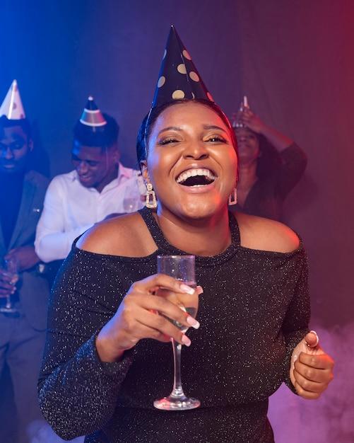 Mulher mostrando sua taça de champanhe e rindo Foto gratuita