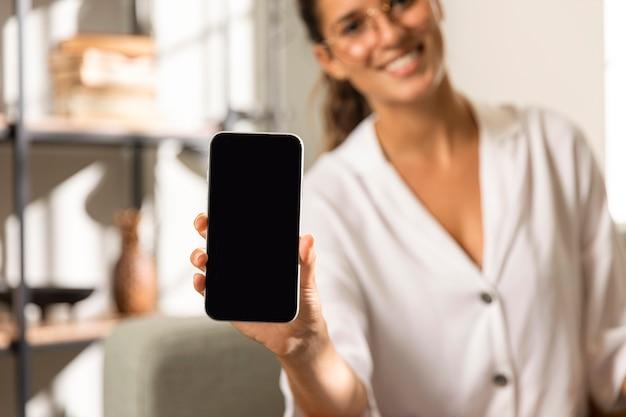 Mulher mostrando telefone de prancha Foto gratuita