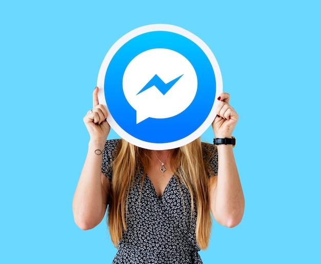 Mulher mostrando um ícone do facebook messenger Foto gratuita