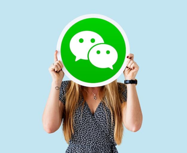 Mulher mostrando um ícone do wechat Foto gratuita