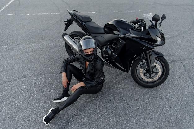 Mulher motociclista na jaqueta de couro preta e capacete facial senta-se perto de moto esportiva elegante no estacionamento urbano. viajando e conceito de estilo de vida ativo. Foto Premium