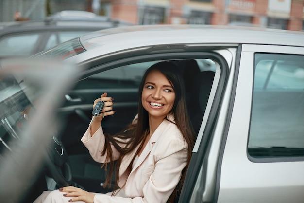 Mulher, motorista de carro sorrindo, mostrando as novas chaves do carro Foto Premium