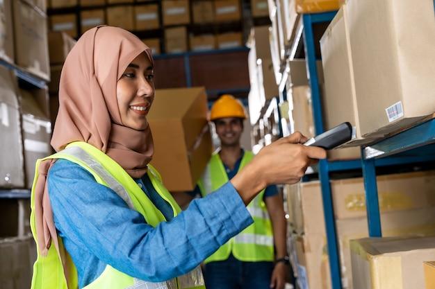 Mulher muçulmana asiática no depósito faz inventário com leitor de código de barras Foto Premium