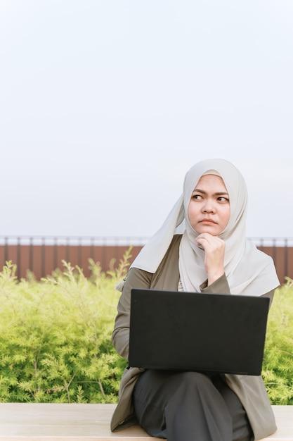 Mulher muçulmana asiática nova pensativa no terno verde e trabalho em um computador no parque. mão perto do rosto. Foto Premium