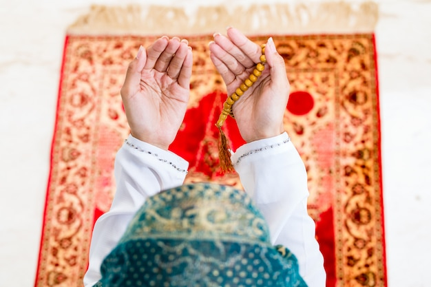 Mulher muçulmana asiática rezando com corrente de grânulos Foto Premium