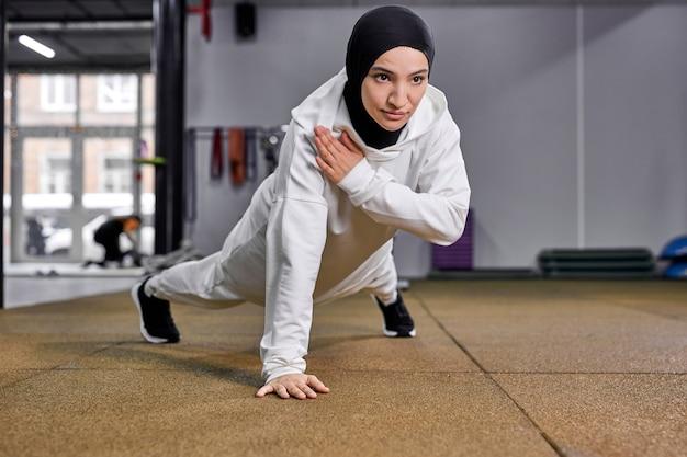 Mulher muçulmana desportiva fazendo flexões, mulher de fitness malhando exercícios de prancha. mulher motivada em hijab gosta de treinar no chão na academia Foto Premium