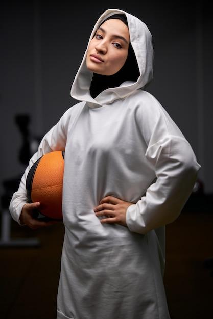 Mulher muçulmana em pé com uma bola de basquete, posando para a câmera após o treino, jovem mulher praticando esportes, usando hijab Foto Premium