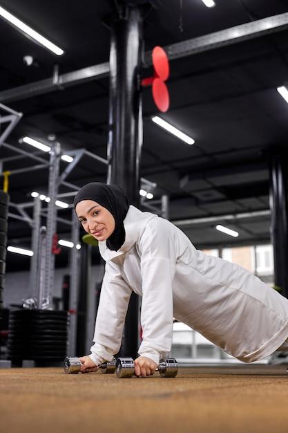 Mulher muçulmana forte fazendo uma série de flexões em uma academia, mulher atleta esportiva em hijab concentrada no treino, usando halteres Foto Premium