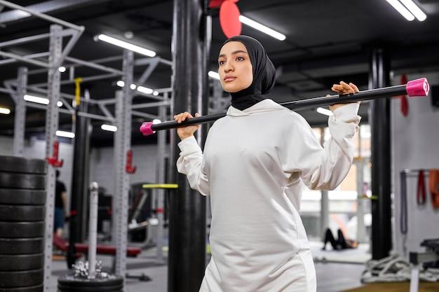Mulher muçulmana, levantando a barra vazia durante o treinamento de treino de esporte no ginásio de fitness moderno. conceito de estilo de vida saudável e esporte Foto Premium