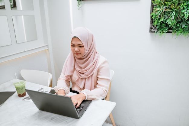 Mulher muçulmana nova que usa o portátil preto. mulher de negócios asiática nova que senta-se na cafetaria e que trabalha no portátil. Foto Premium