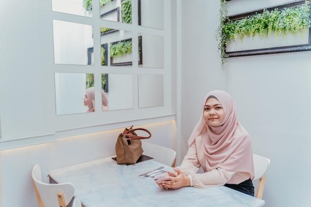 Mulher muçulmana nova segura que senta-se na cadeira branca e que relaxa na cafetaria no dia de férias. Foto Premium