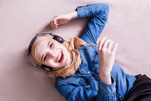 Mulher muçulmana ouvindo música em fones de ouvido Foto gratuita