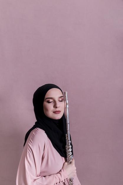 Mulher muçulmana tocando flauta Foto gratuita