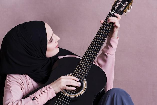 Mulher muçulmana tocando guitarra Foto gratuita