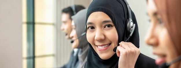 Mulher muçulmana, trabalhando como operador de serviço ao cliente com equipe em call center Foto Premium