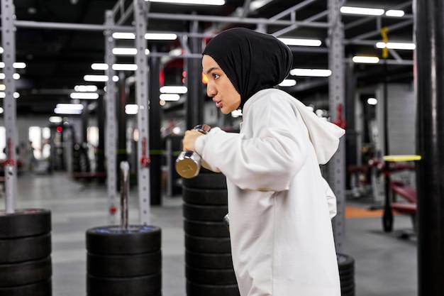 Mulher muçulmana treinando na academia usando halteres, fazendo exercícios intensos sozinhas em uma academia moderna, usando um hijab esportivo branco Foto Premium