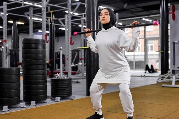 Mulher muçulmana usando hijab fazendo um agachamento com musculação para estar em forma, atlética e saudável no futuro. jovem está concentrada no fitness Foto Premium