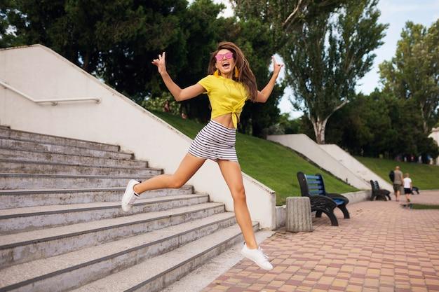 Mulher muito jovem e sorridente se divertindo no parque da cidade, pulando escadas, positivo, emocional, vestindo blusa amarela, minissaia listrada, óculos de sol rosa, tênis branco, tendência da moda no estilo de verão Foto gratuita