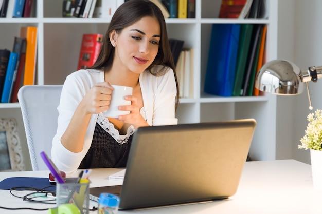 Mulher muito jovem trabalhando com laptop em seu for Bankia oficina de internet entrar