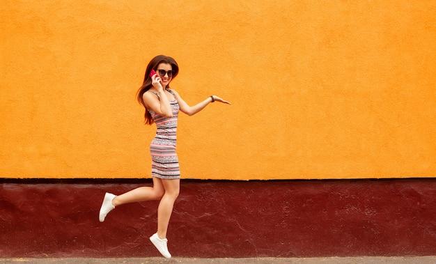 Mulher muito sorridente em óculos de sol falando no smartphone contra a parede laranja Foto Premium