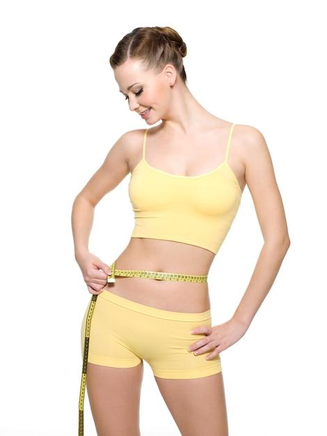 Mulher muito sorridente medindo a cintura com o tipo de medição isolado no branco Foto gratuita