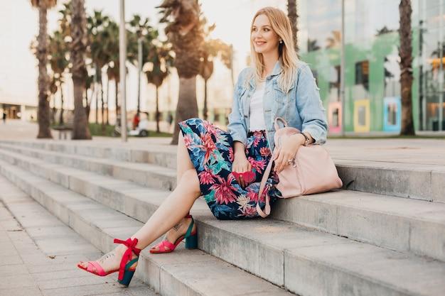 Mulher muito sorridente, sentada na escada em uma rua da cidade, com saia estampada elegante e jaqueta jeans grande e mochila de couro, tendência do verão Foto gratuita