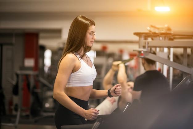 Mulher na academia em uma máquina de correr Foto gratuita