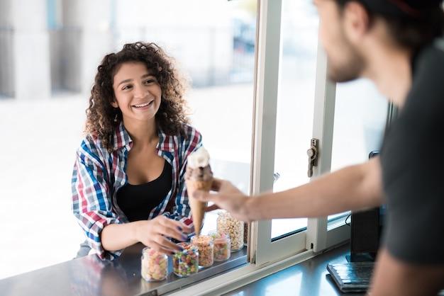 Mulher na camisa comprando sorvete no caminhão de comida. Foto Premium