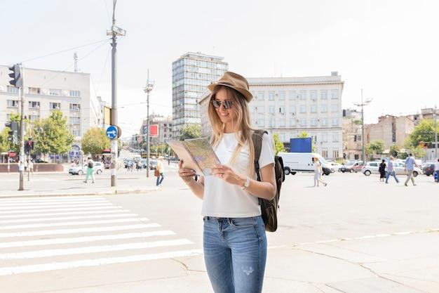 Mulher na cidade olhando para o mapa Foto gratuita