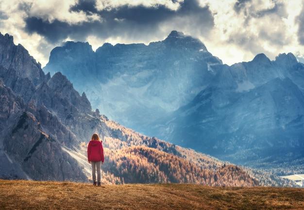 Mulher na colina está olhando para as montanhas majestosas ao pôr do sol Foto Premium