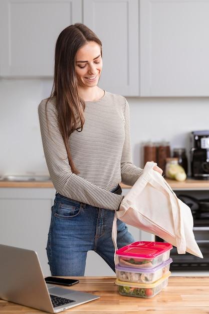 Mulher na cozinha com comida e computador portátil Foto gratuita