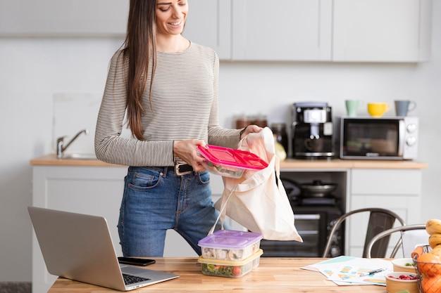 Mulher na cozinha com laptop e comida Foto gratuita