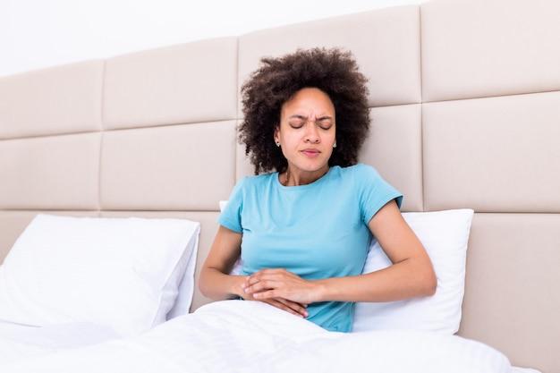 Mulher na expressão dolorosa, segurando as mãos contra a barriga com dores do período menstrual, deitado triste na cama em casa Foto Premium