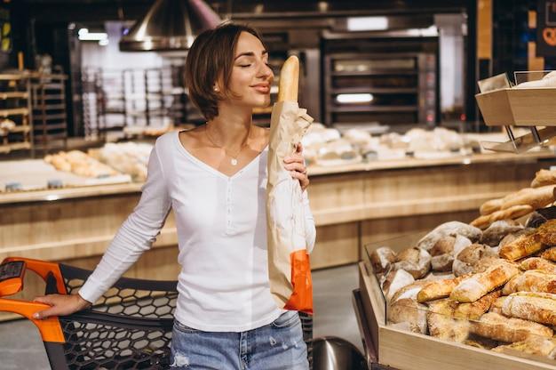 Mulher na mercearia comprar pão fresco Foto gratuita