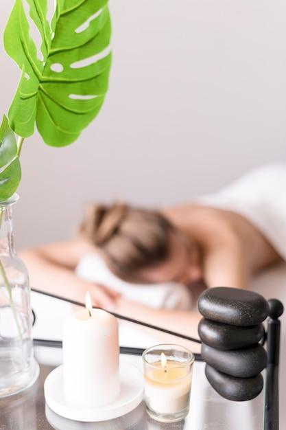 Mulher na mesa de massagem com vela Foto gratuita